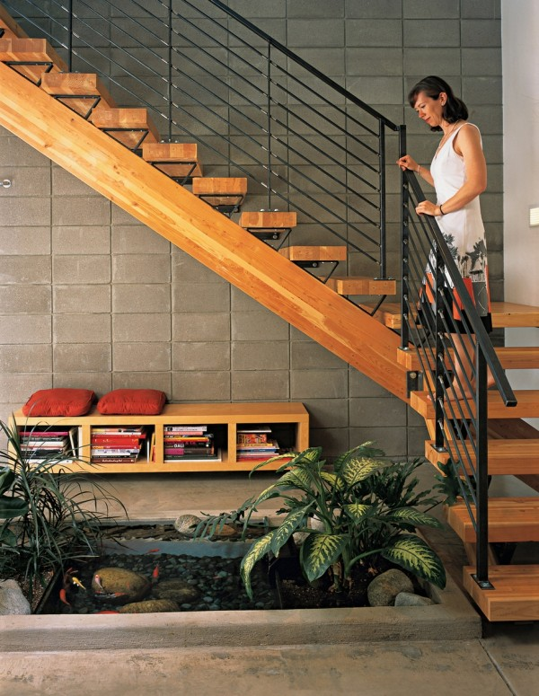 Dwell-indoor-fish-pond-viewed-from-rich-wooden-staircase-600x775